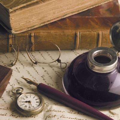 Libros antiguos, un tintero, un plumín, un reloj, un folio, unas gafas...
